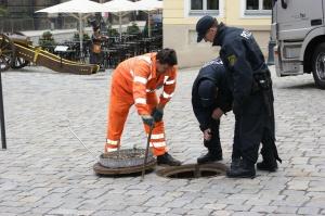 Polizisten und Arbeiter kontrollieren Gullys vor der Frauenkirche.